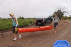 Na lama e na chuva, carregando os equipamentos para a partida.